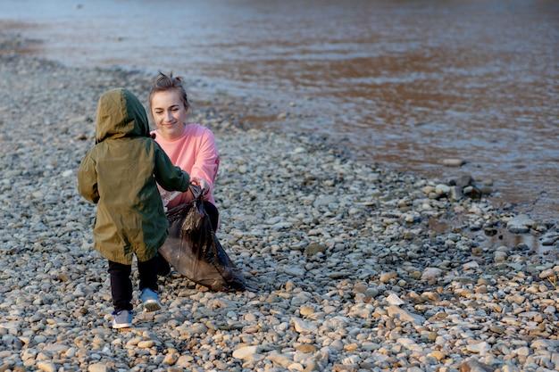 Junge frau mit ihrem sohn sammelt plastikmüll in einem müllsack auf dem fluss