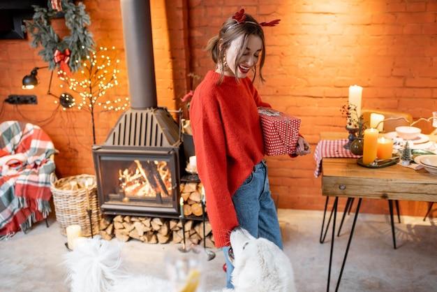 Junge frau mit ihrem süßen hund, der sich zu hause am kamin und am esstisch auf neujahrsferien vorbereitet