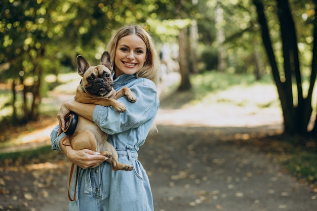 Junge frau mit ihrer französischen bulldogge des haustieres im park