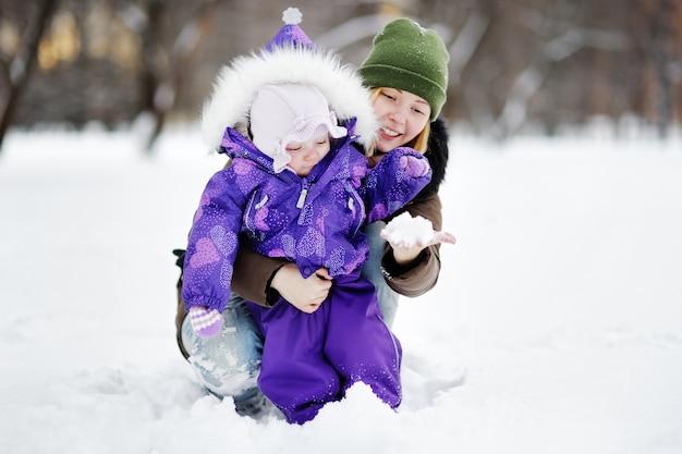 Junge frau mit ihrer kleinkindtochter, die mit schnee am winterpark spielt