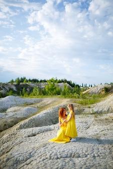 Junge frau mit ihrer tochter in einem gelben kleid nahe dem see mit azurblauem wasser und grünen bäumen. glückliches familienbeziehungskonzept