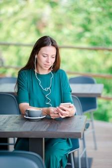 Junge frau mit intelligentem telefon beim in der kaffeestube während der freizeit allein sitzen