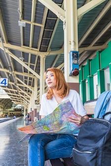 Junge Frau mit Karte auf der Plattform