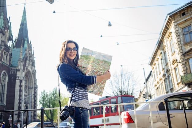 Junge frau mit karte im alten stadtzentrum