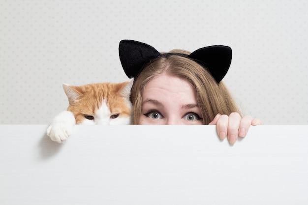 Junge frau mit katze versteckt sich hinter einem weißen banner