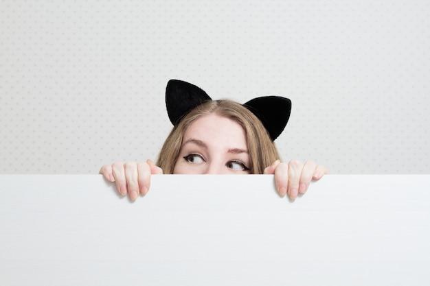 Junge frau mit katzenohren auf dem kopf späht aus einem weißen banner heraus und schaut weg