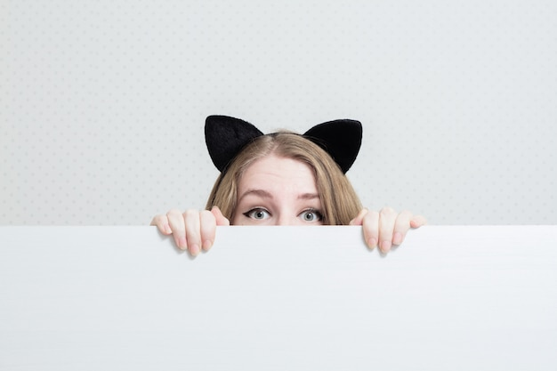 Junge frau mit katzenohren auf dem kopf späht aus einem weißen banner heraus