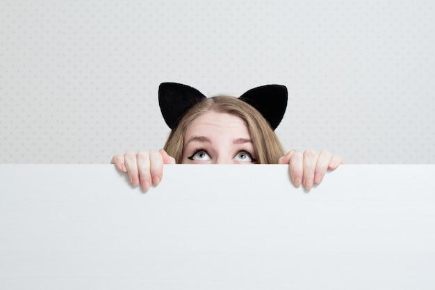 Junge frau mit katzenohren auf ihrem kopf späht aus einem weißen banner heraus und schaut auf