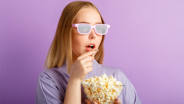 Junge frau mit kinobrille, die einen 3d-film im kino sieht. lächelnder teenager-mädchen-film-viewer in gläsern, die popcorn essen, isoliert über lila farbhintergrund mit kopierraum. langes webbanner.