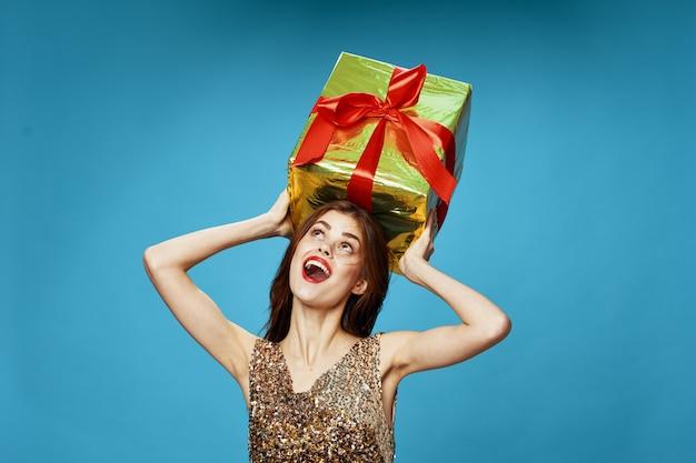 Junge frau mit kisten von geschenken in ihren händen im studio auf einer farbigen oberfläche in schönen kleidern, verkauf von geschenken, frohen weihnachten und neujahr