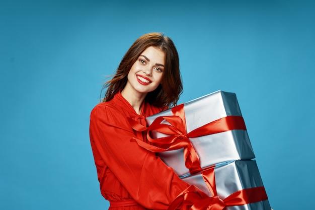 Junge frau mit kisten von geschenken in ihren händen in den schönen kleidern, verkaufende geschenke, frohe weihnachten und neujahr