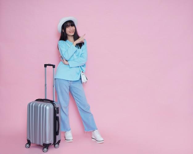 Junge frau mit koffer auf rosa wand