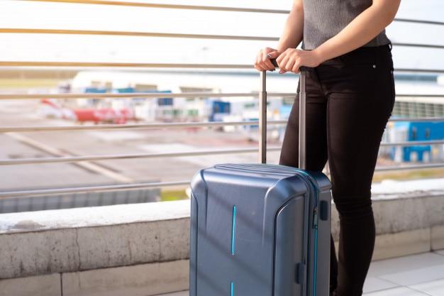 Junge frau mit koffer in airtport