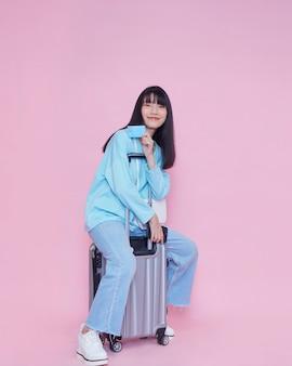 Junge frau mit koffer und kreditkarte auf farbwand. sommerreise