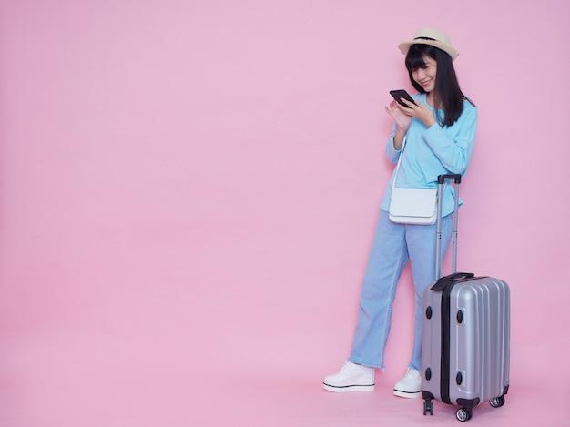 Junge frau mit koffer und smartphone auf rosa wand
