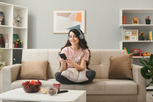 Junge frau mit kopfhörern, die das telefon auf dem sofa hinter dem couchtisch im wohnzimmer hält und betrachtet