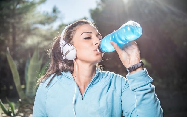 Junge frau mit kopfhörern, die nach dem laufen aus einer plastikflasche ruht und trinkt