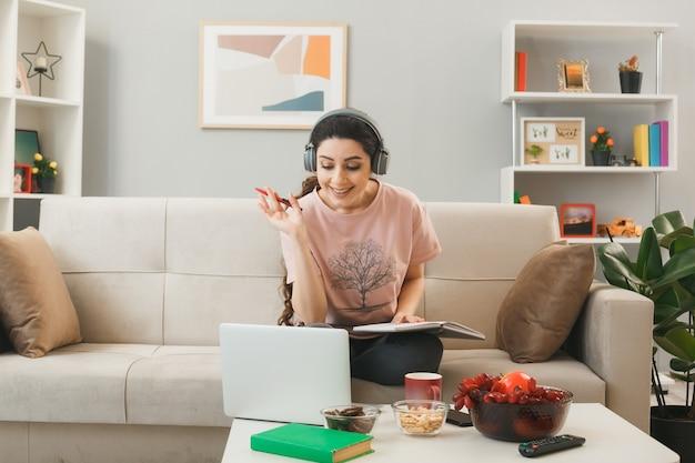 Junge frau mit kopfhörern, die stift mit buch hält, benutzte laptop, der auf dem sofa hinter dem couchtisch im wohnzimmer sitzt?