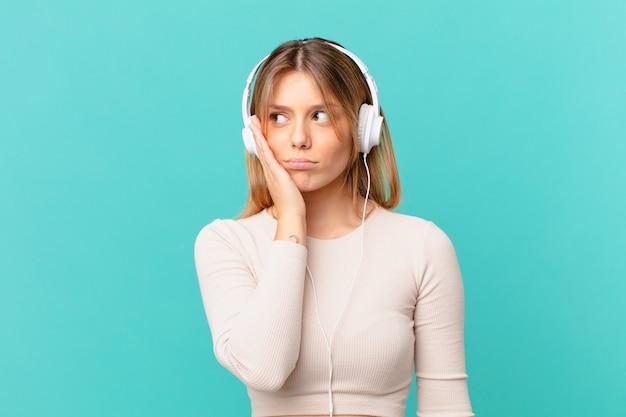 Junge frau mit kopfhörern gelangweilt, frustriert und schläfrig nach einem ermüdenden