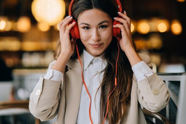 Junge frau mit kopfhörern hören musik, während sie in cafés sitzt
