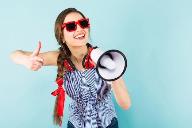 Junge frau mit kopfhörern und lautsprecher