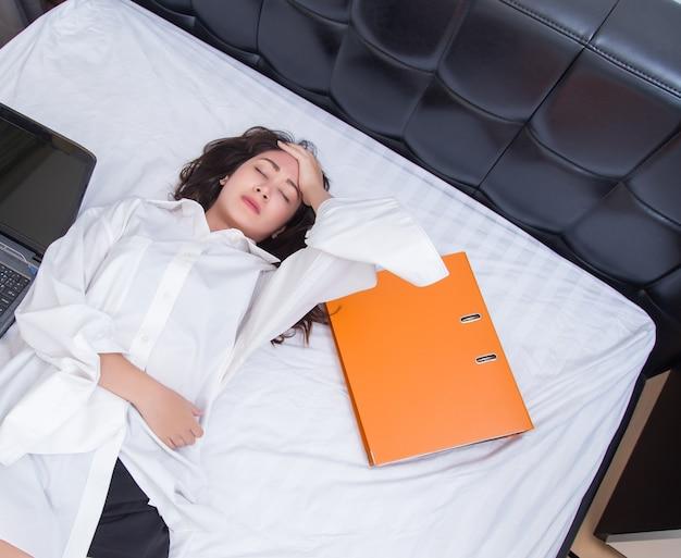 Junge frau mit kopfschmerzen auf ihrem bett. konzept für gesund und geschäft