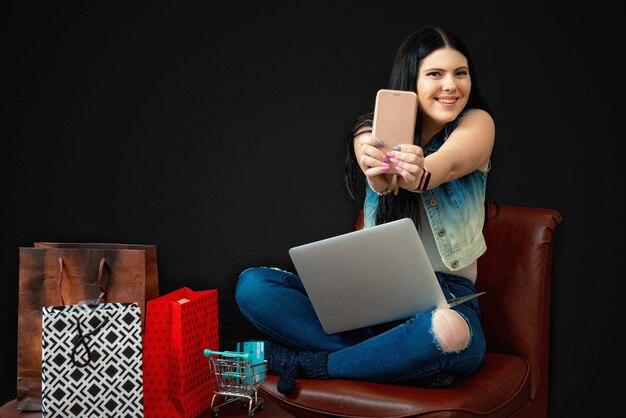 Junge frau mit kreditkarte, die laptop für online-einkauf verwendet, lokalisiert auf schwarz