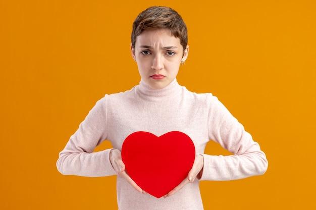 Junge frau mit kurzem haar, das herz aus pappe mit traurigem ausdruck valentinstagkonzept hält, das über orange wand steht