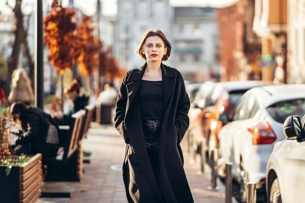 Junge frau mit kurzem haarschnitt, gekleidet in einen schwarzen mantel, der durch die straßen der stadt schlendert. herum sind menschen und autos.