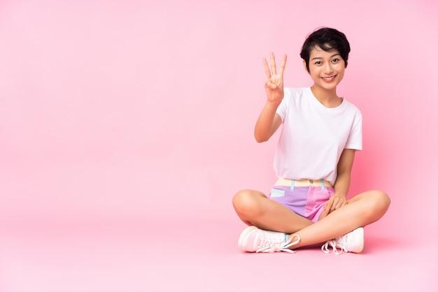 Junge frau mit kurzen haaren, die auf dem boden über isoliertem rosa glücklich sitzen und drei mit den fingern zählen