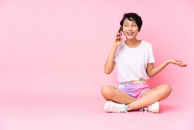 Junge frau mit kurzen haaren, die auf dem boden über rosa wand sitzen und ein gespräch mit dem mobiltelefon mit jemandem halten