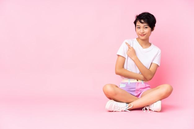 Junge frau mit kurzen haaren, die auf dem boden über vereinzeltem rosa sitzen, das zur seite zeigt, um ein produkt zu präsentieren