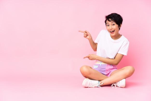 Junge frau mit kurzen haaren, die auf dem boden über vereinzeltem rosa überraschtem und zeigendem seite sitzen
