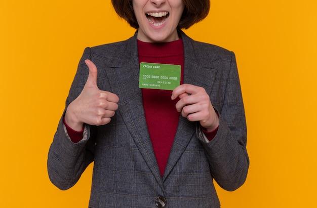 Junge frau mit kurzen haaren, die graue jacke hält, die kreditkarte hält