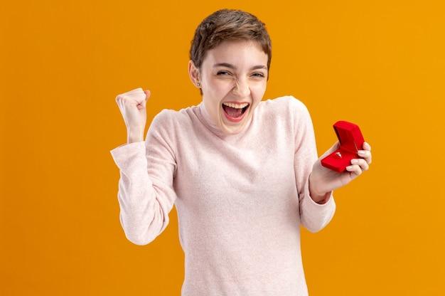 Junge frau mit kurzen haaren, die rote box mit verlobungsring glücklich und aufgeregt geballt faust glücklich und aufgeregt valentinstag konzept steht über orange wand halten