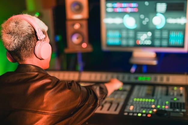 Junge frau mit kurzen haaren, die spaß beim mischen von musik im aufnahmestudio hat - musikstudiokonzept