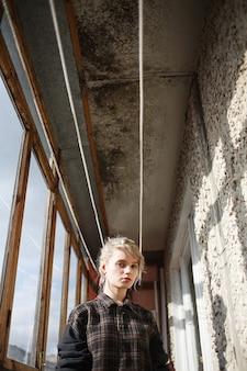 Junge frau mit kurzen haaren in kariertem hemd, die in der nähe des balkonfensters steht