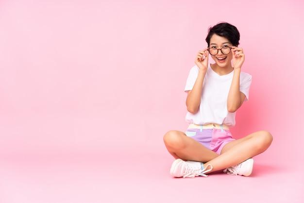Junge frau mit kurzen haaren sitzt auf dem boden über isoliertem rosa mit brille und überrascht