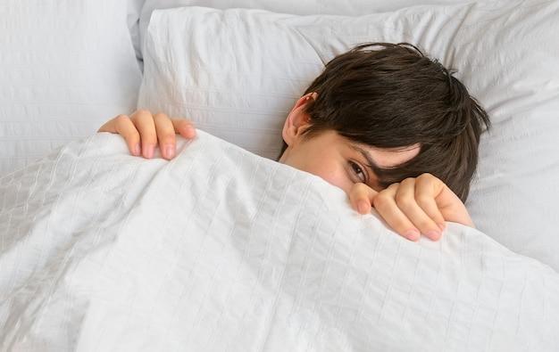 Junge frau mit kurzen haaren späht unter der decke hervor und wacht morgens im bett auf