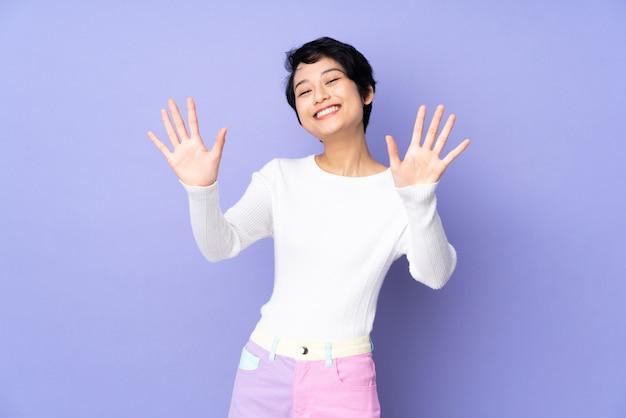 Junge frau mit kurzen haaren über isoliertem purpur, das zehn mit den fingern zählt