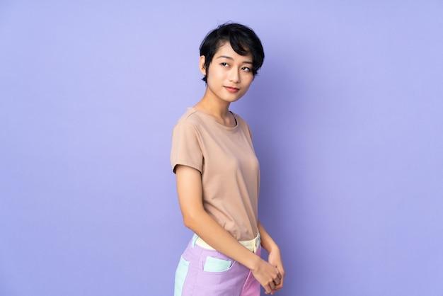 Junge frau mit kurzen haaren über isoliertem purpur
