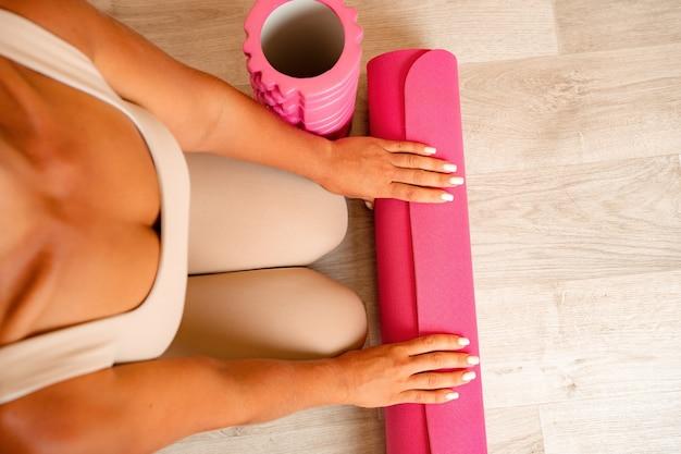 Junge frau mit langem haar-fitness-lehrer in beige sportkleidung, die sich auf das dehnen vorbereitet und