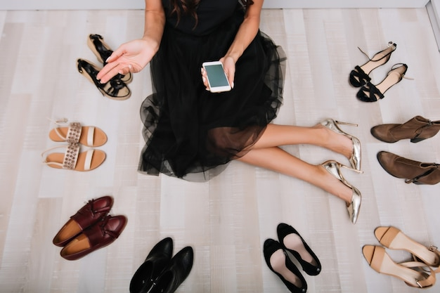 Junge frau mit langen beinen, die auf boden im kleiderschrank mit smartphone in händen sitzen, nachricht schreiben, internet suchen. viele schuhe herum. trägt schwarzen schönen rock, silberne stilvolle high heels.
