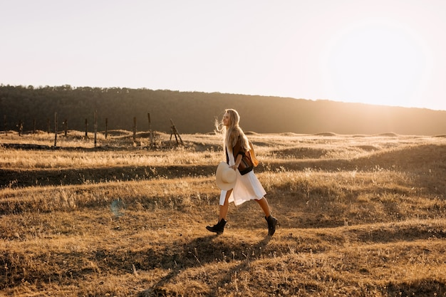 Junge frau mit langen blonden haaren, läuft in einem feld mit trockenem gras