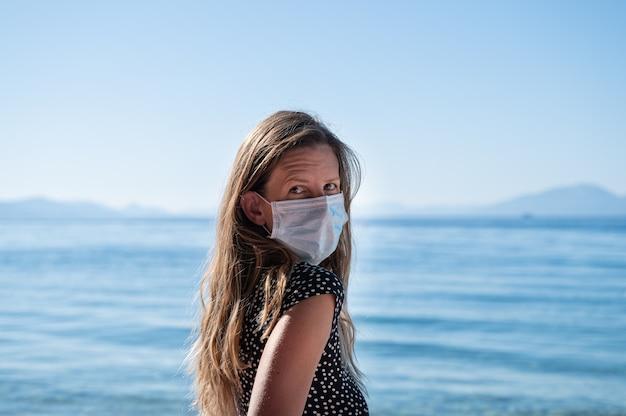 Junge frau mit langen braunen haaren, die medizinische schutzmaske tragen, während sie neben einem schönen blauen meer stehen.