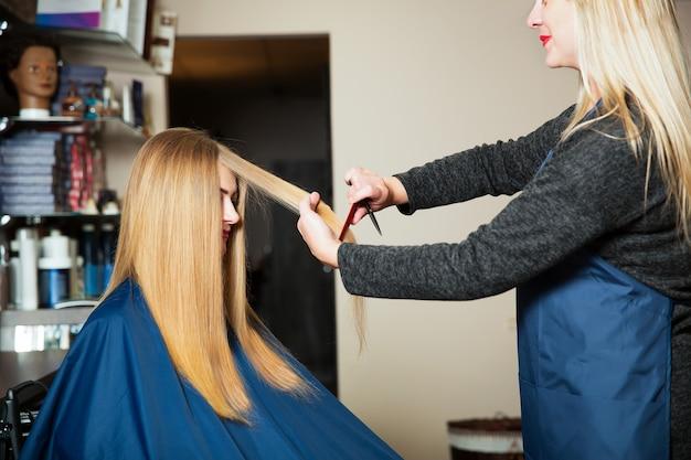 Junge frau mit langen haaren beim friseur. stylistin, die frisur mit schere und kamm macht.