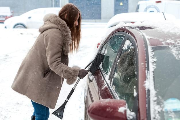 Junge frau mit langen haaren, die auto nach schneesturm säubert