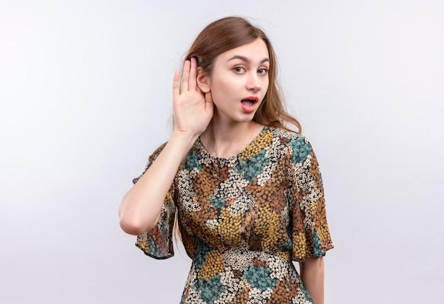 Junge frau mit langen haaren, die buntes kleid tragen, das mit hand nahe ohr steht und versucht, jemandes gespräch über weiße wand zu hören