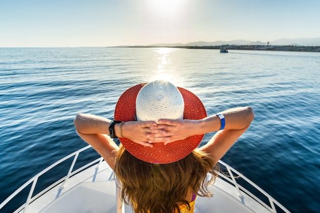 Junge frau mit langen haaren, die einen strohhut tragen, der auf weißem yachtdeck steht und blick auf blaues meerwasser genießt.