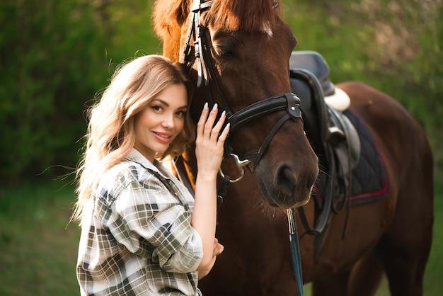 Junge frau mit langen haaren posiert mit einem braunen pferd in einem wald auf einer sonnigen wiese.